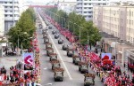 Participants in vehicles drive past in a parade to commemorate the 65th anniversary of the founding of the Workers' Party of Korea in Pyongyang