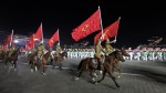 North Korean soldiers ride horses while carry flags of the Workers' Party of Korea during gala evening to commemorate 65th anniversary of founding of party in Pyongyang