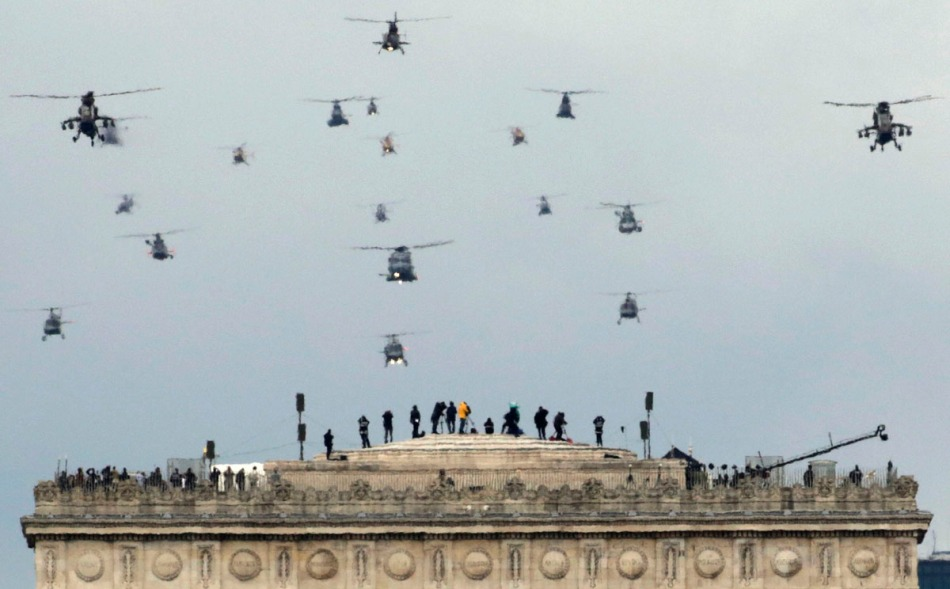 A formation of military helicopters fly over the Arc de Triomphe during the traditional Bastille Day military parade in Paris